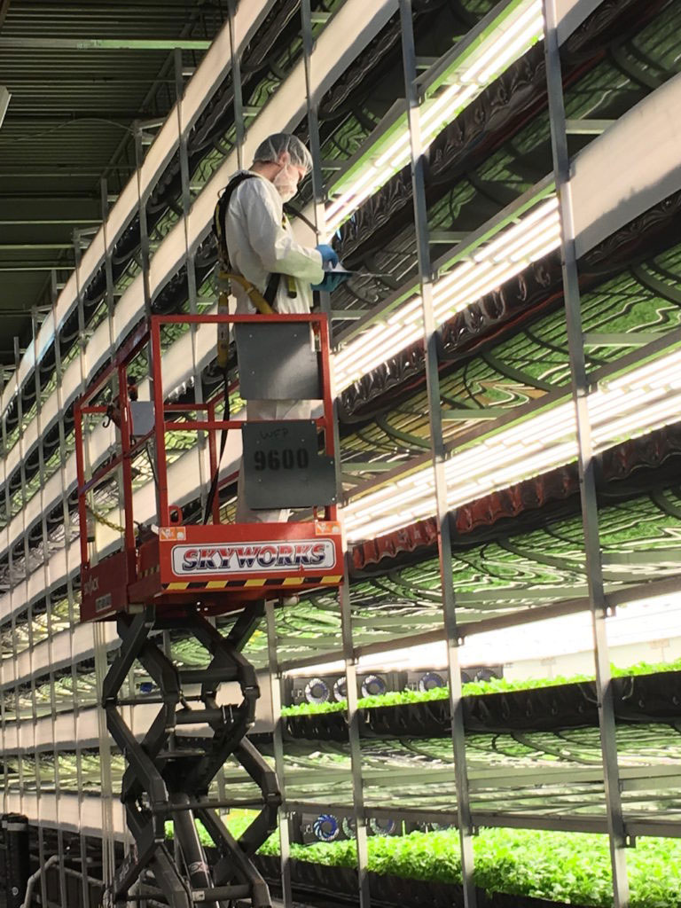 someone in cherry picker next to vertical farm