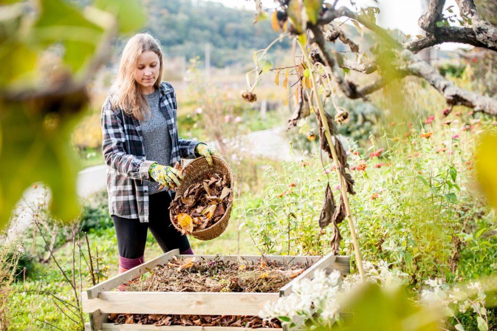 A woman putting food scraps into a compost bin