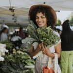 Woman of color purchasing kale from a farmers' market