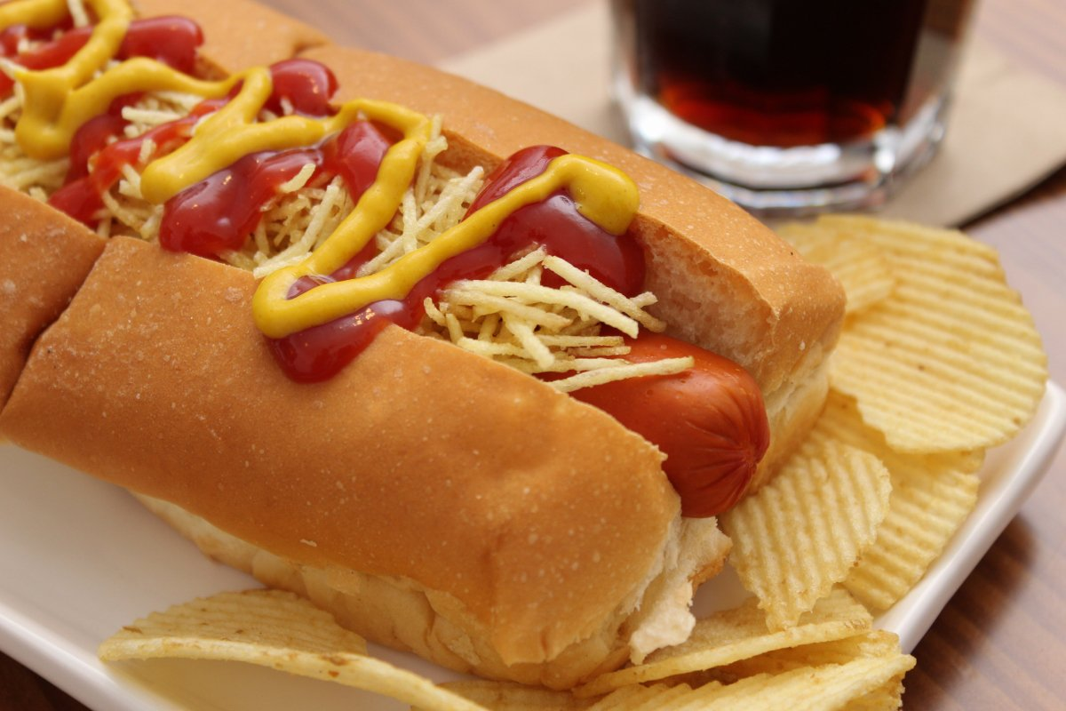 Hot dog with ketchup mustard chips and coke