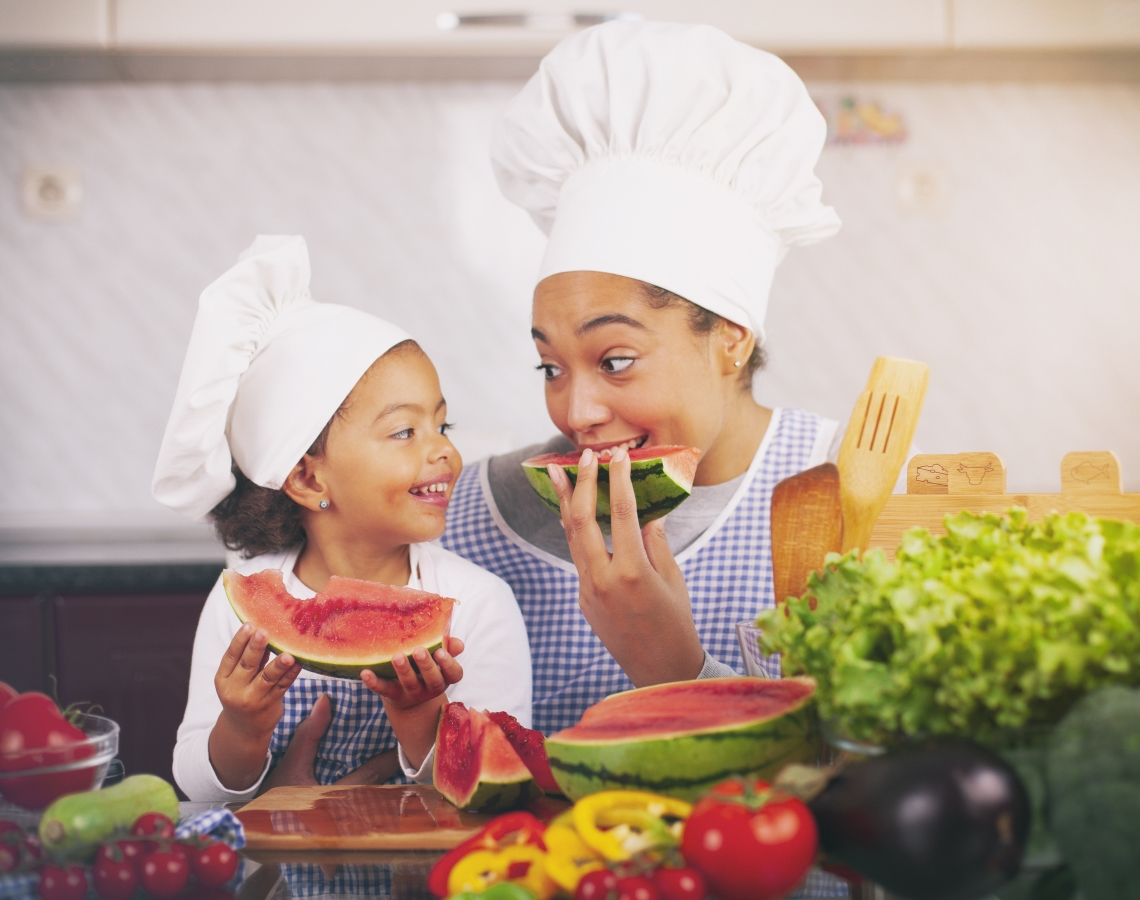 Mother and daughter eating watermelon in the kitchen