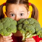 Little girl with two broccoli stalks
