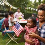 Woman holding her baby holding an American flag