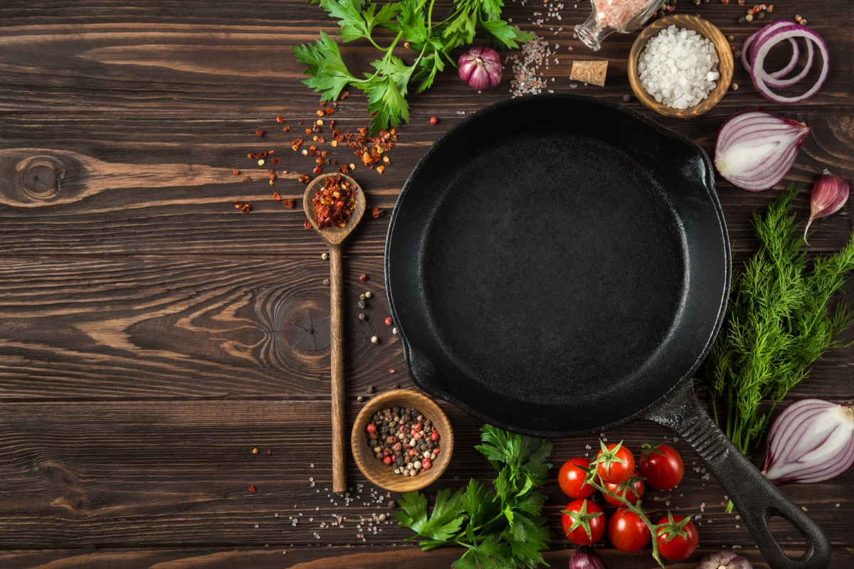 A cast iron pan surrounded by herbs