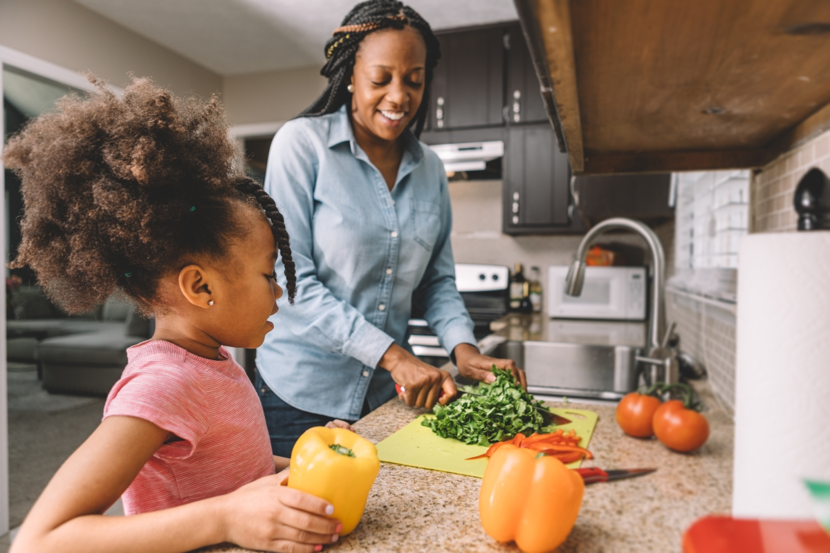 Healthy eating for kids: Mother chops vegetables in kitchen with daughter