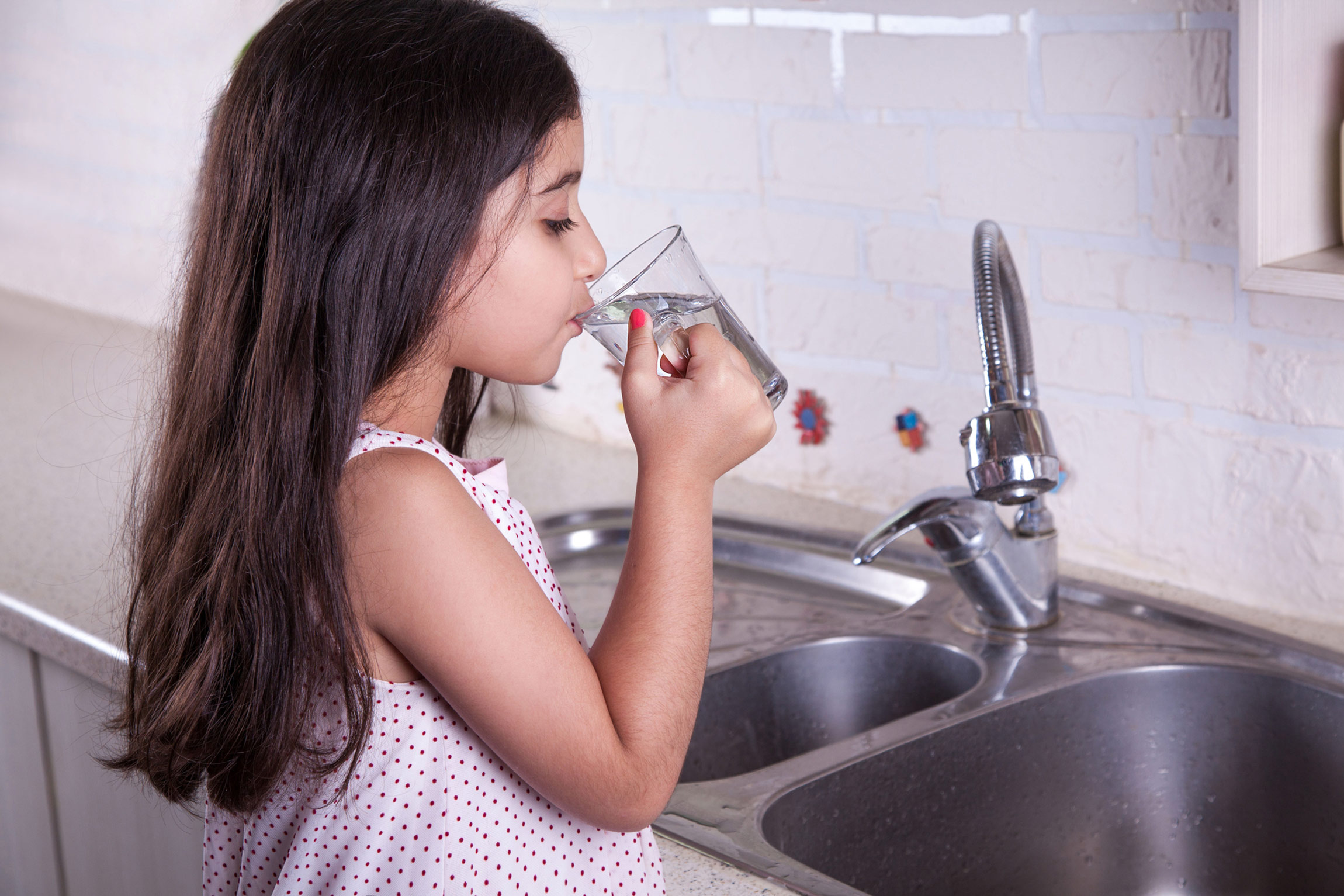 Little girl drinking a glass of tap water