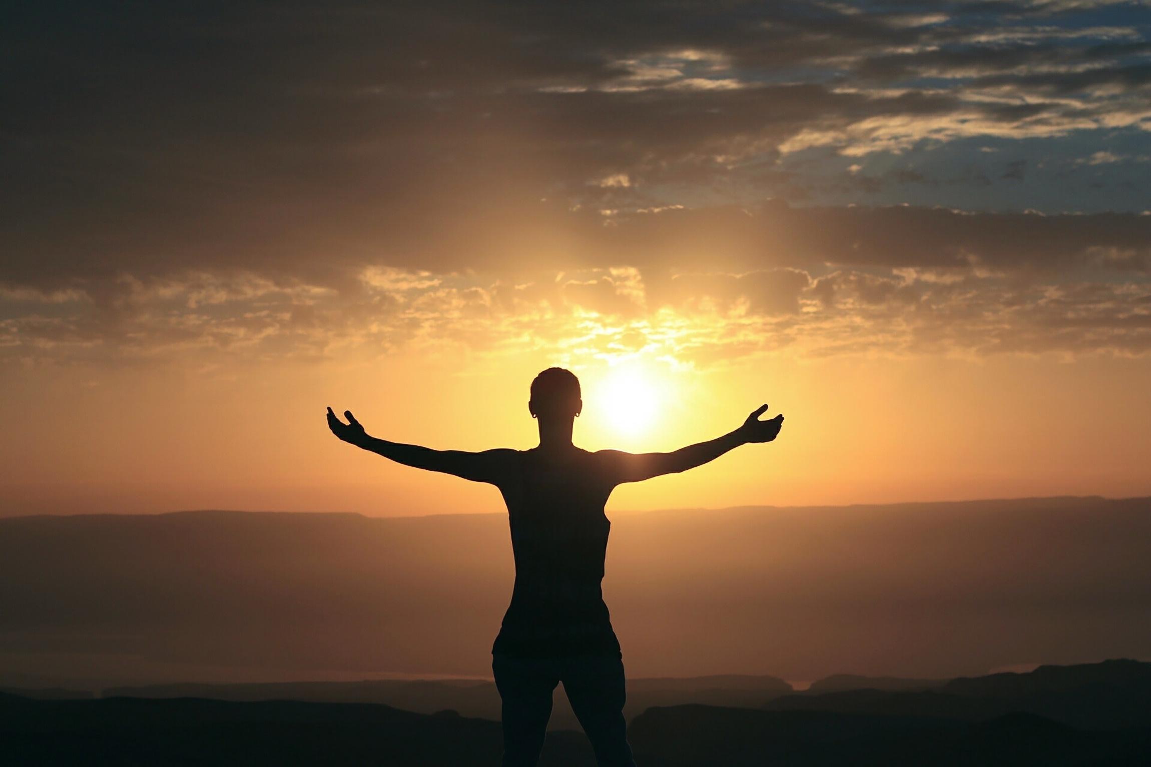 Lifting arms toward sunset