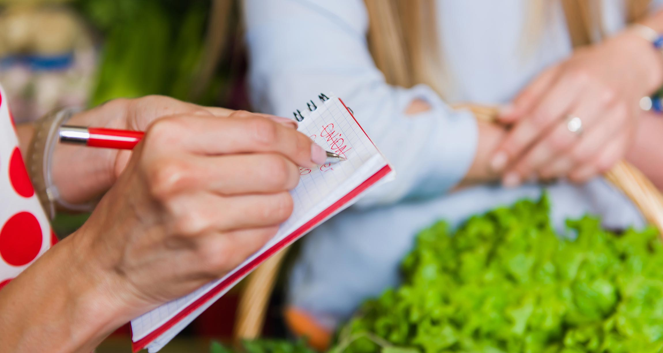 woman crossing item off grocery list