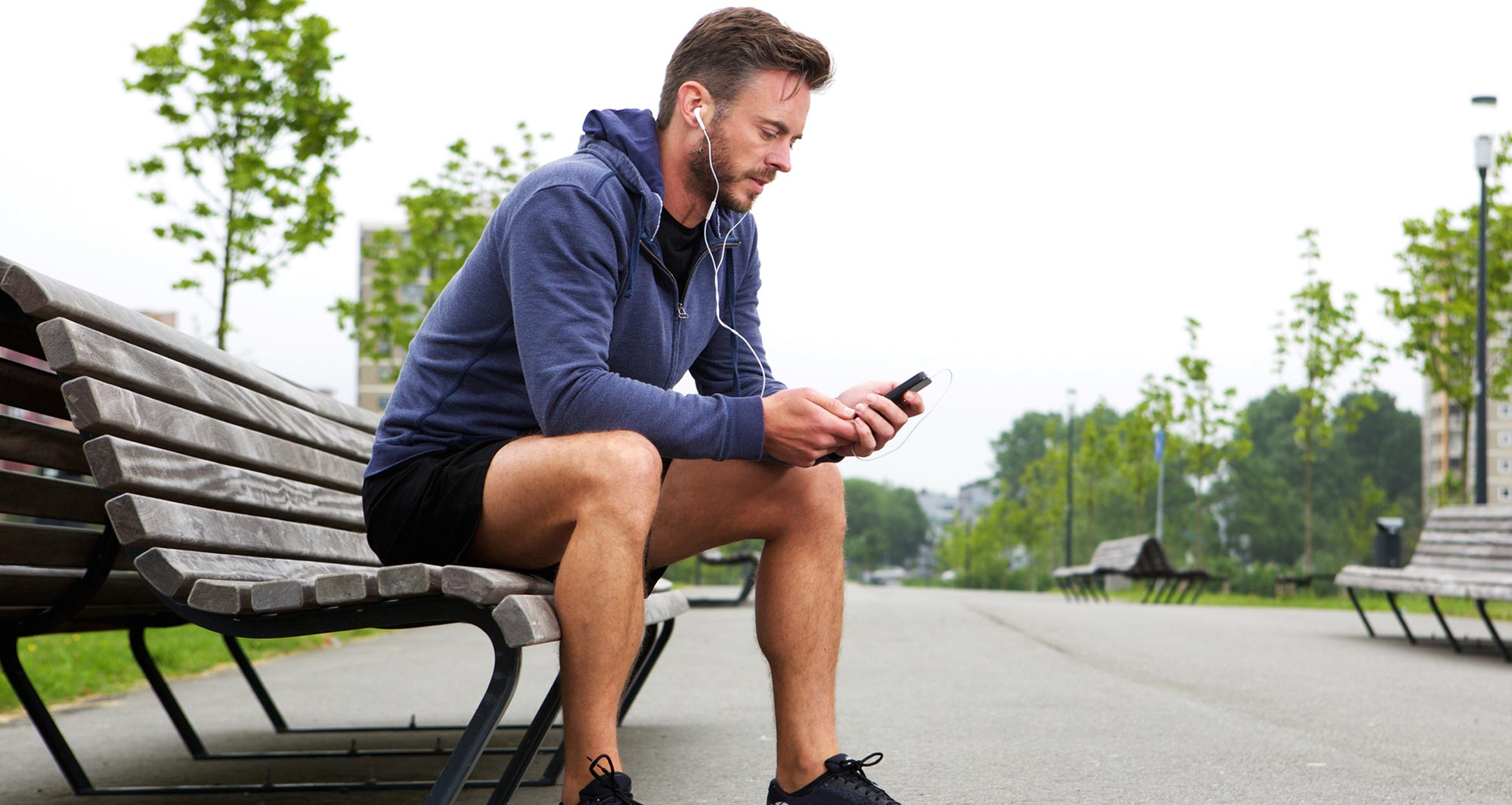 man looking at phone in workout attire