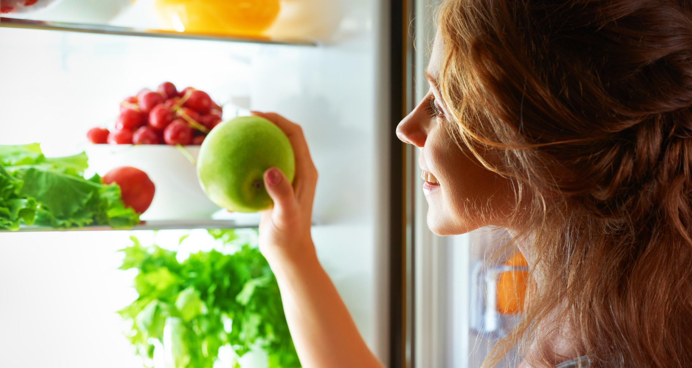 woman looking in fridge with healthy food
