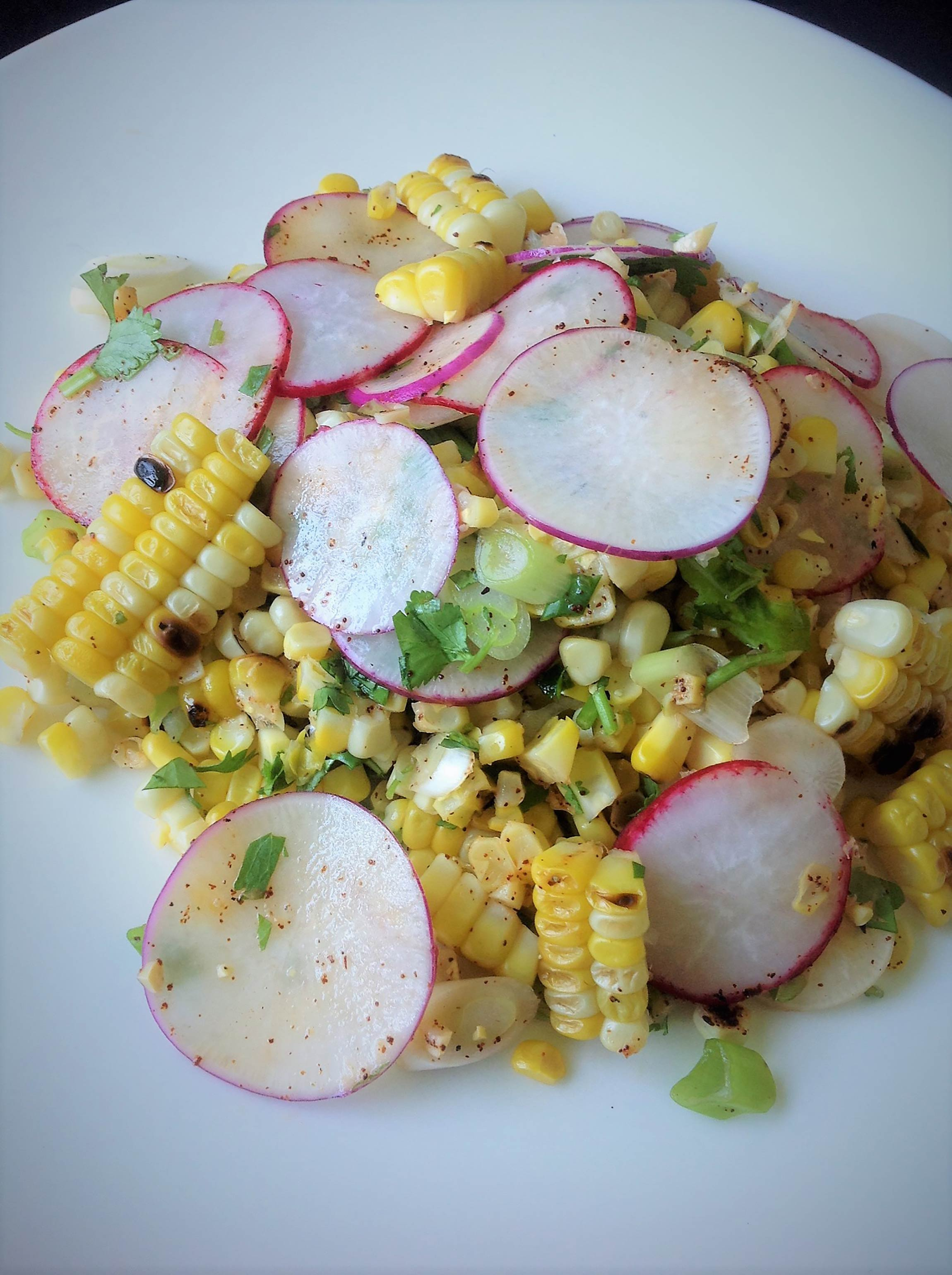 grilled corn and radish salad on a plate