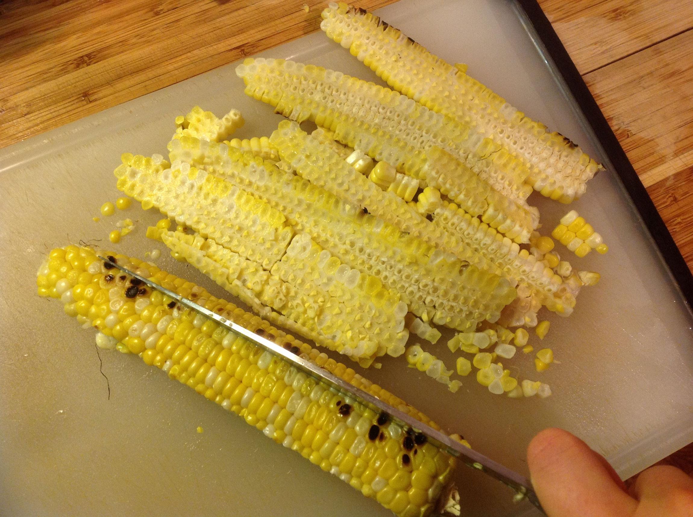 grilled corn being cut on cutting board