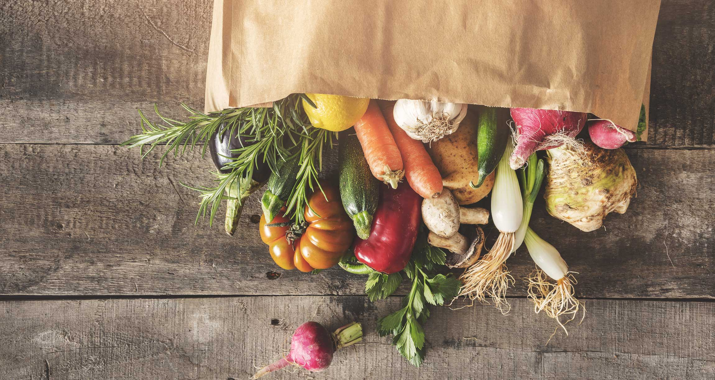 vegetables in a paper bag lying on a table