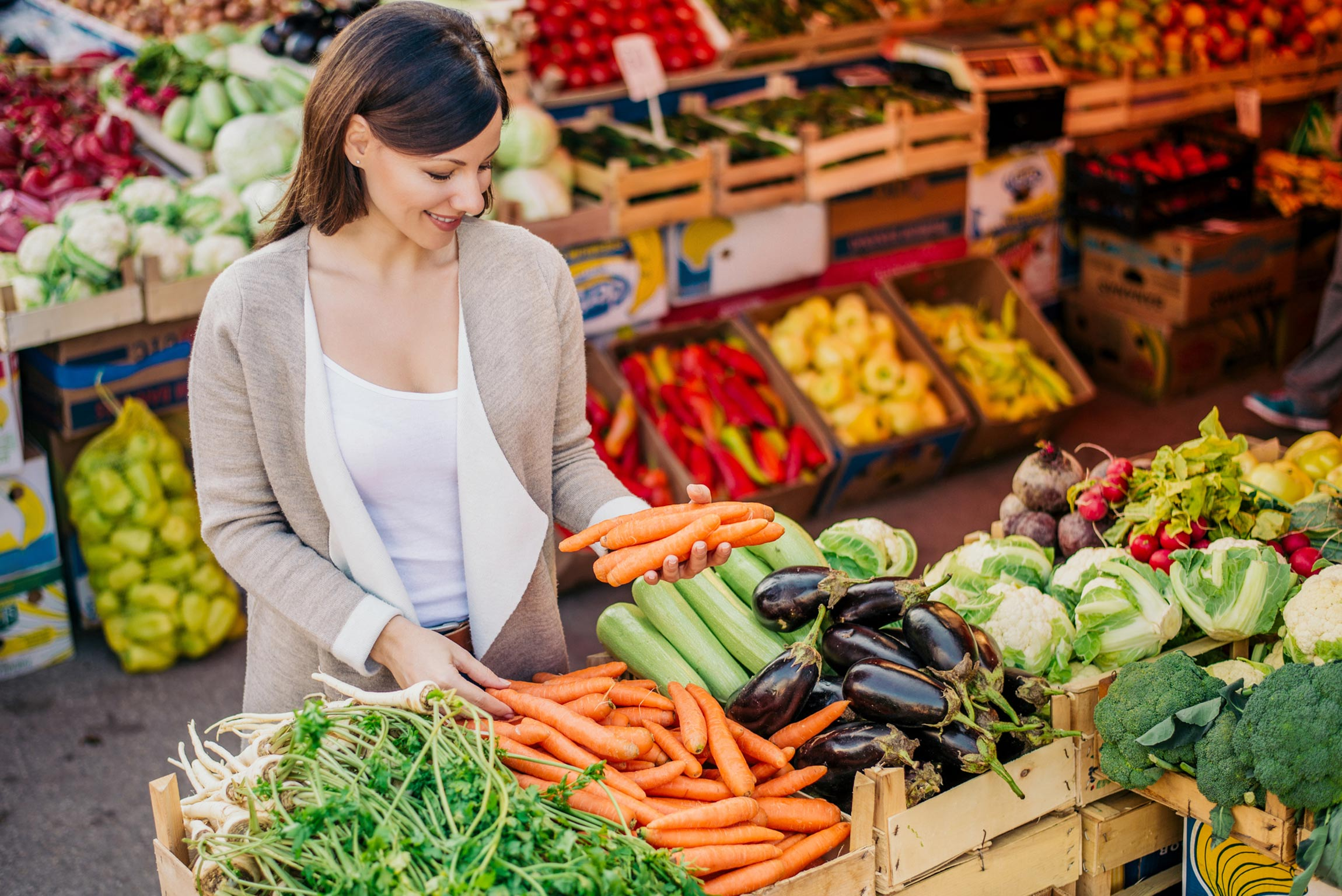 A woman shopping at a farmer's market holding carrots