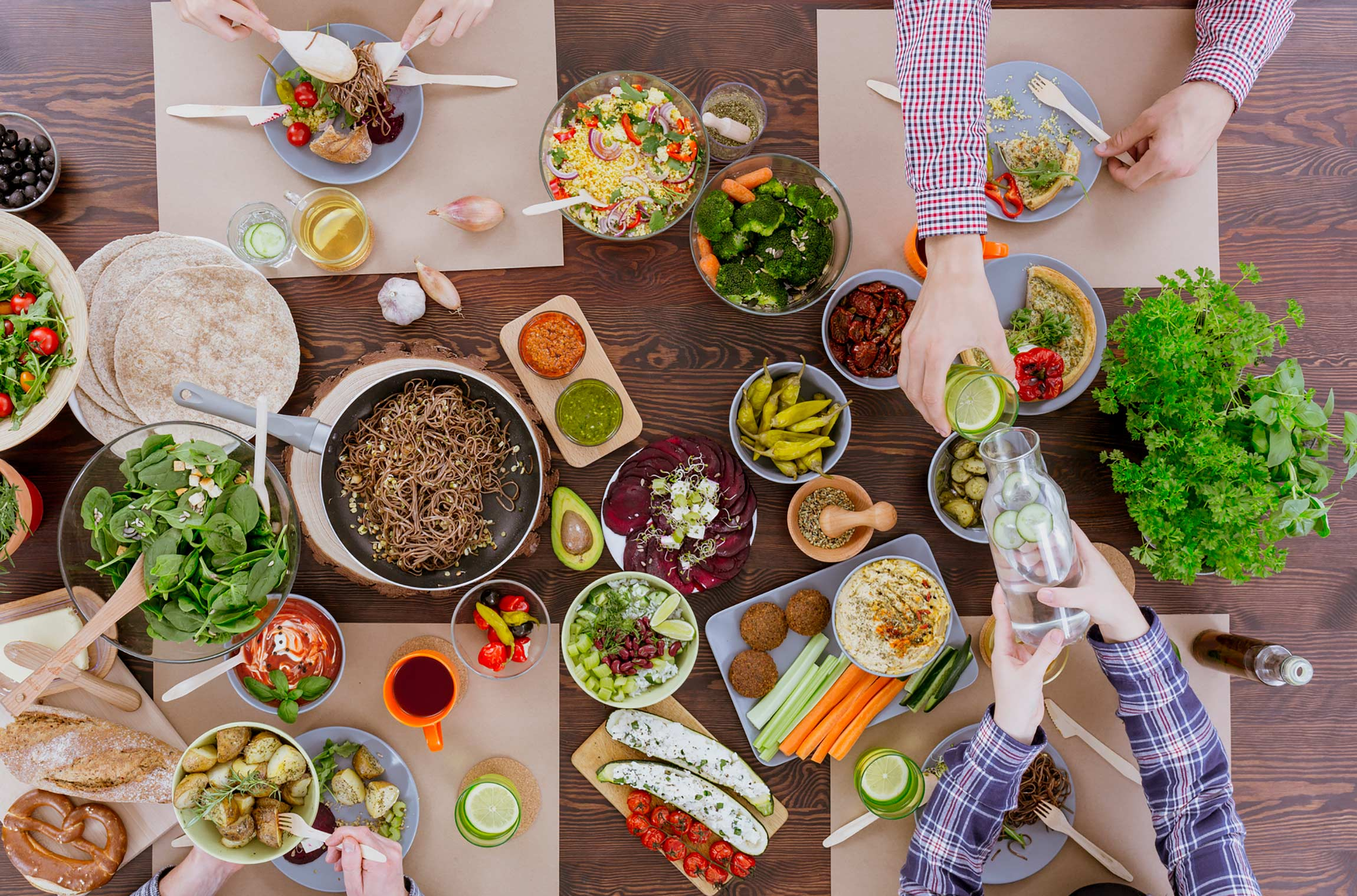 A spread of raw and cooked veggie dishes on a a table