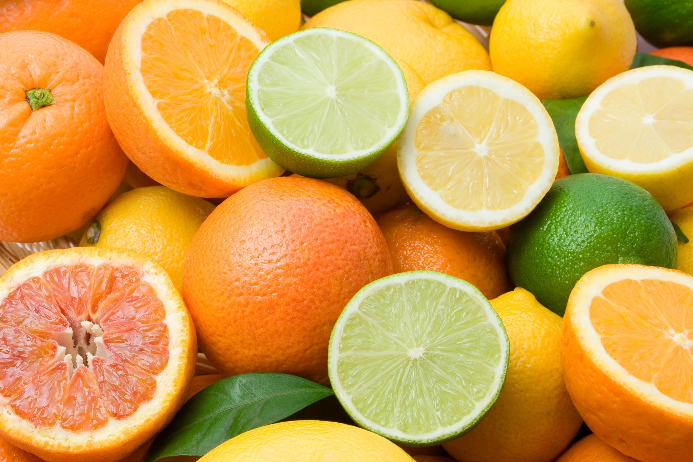 closeup of cut oranges, limes, lemons