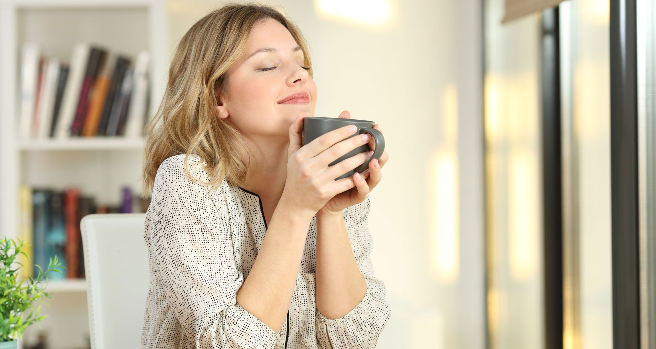 woman enjoying the smell of tea from a mug
