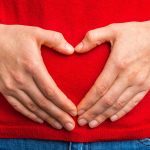 hands in heart shape over the stomach