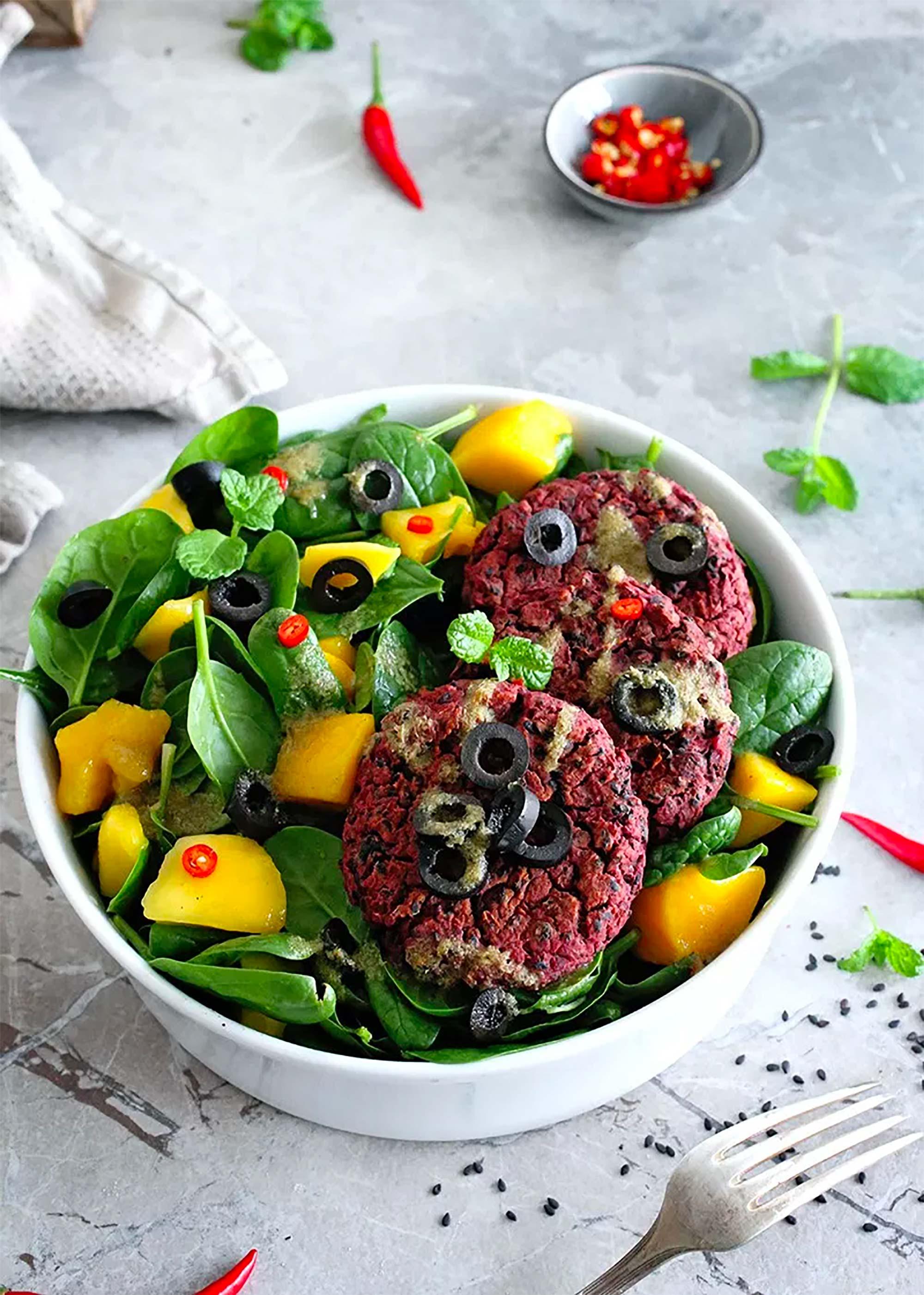 Salatschüssel mit Kartoffel-Patties, Oliven und Mango