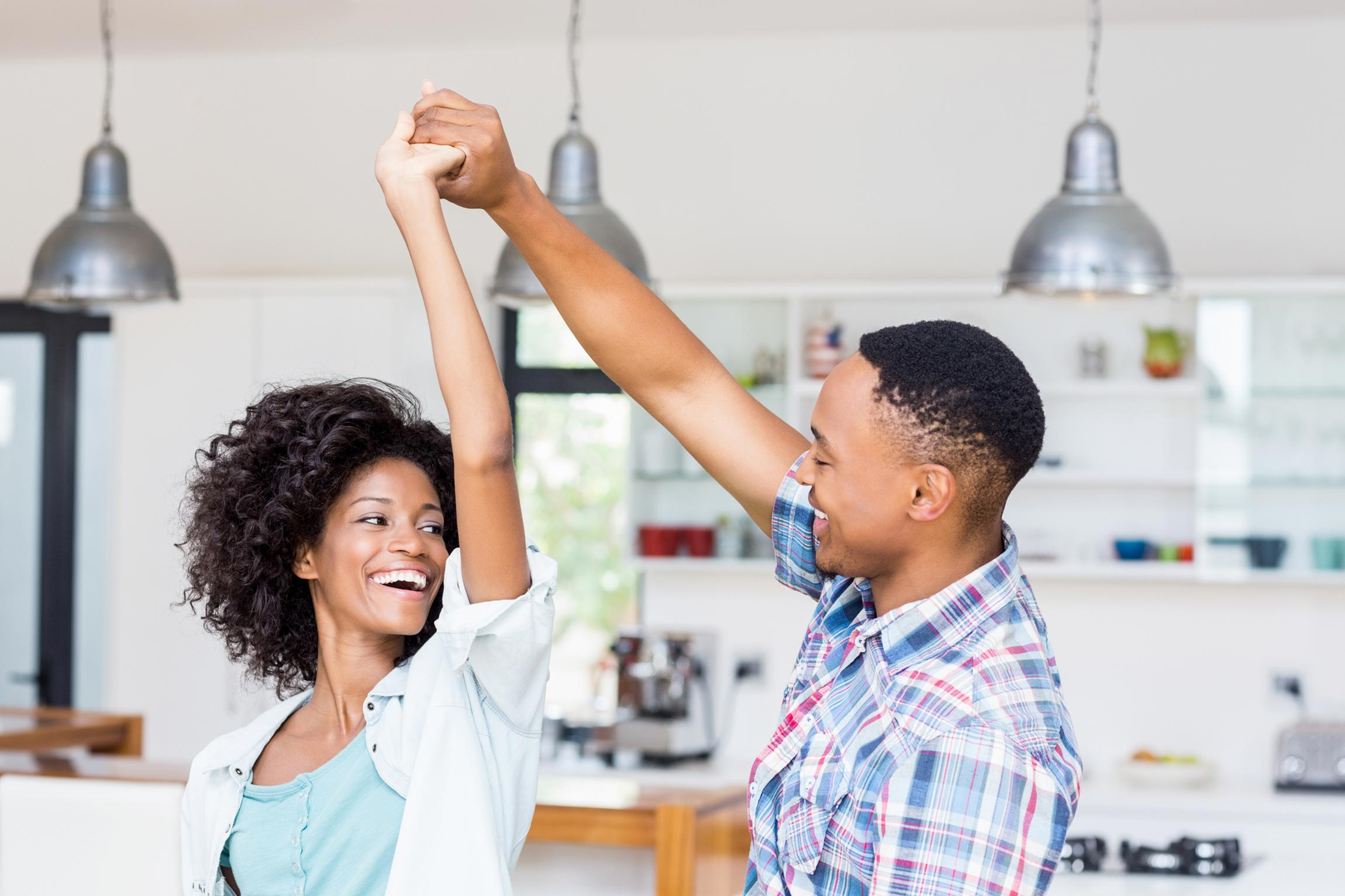 African American couple dancing in kitchen