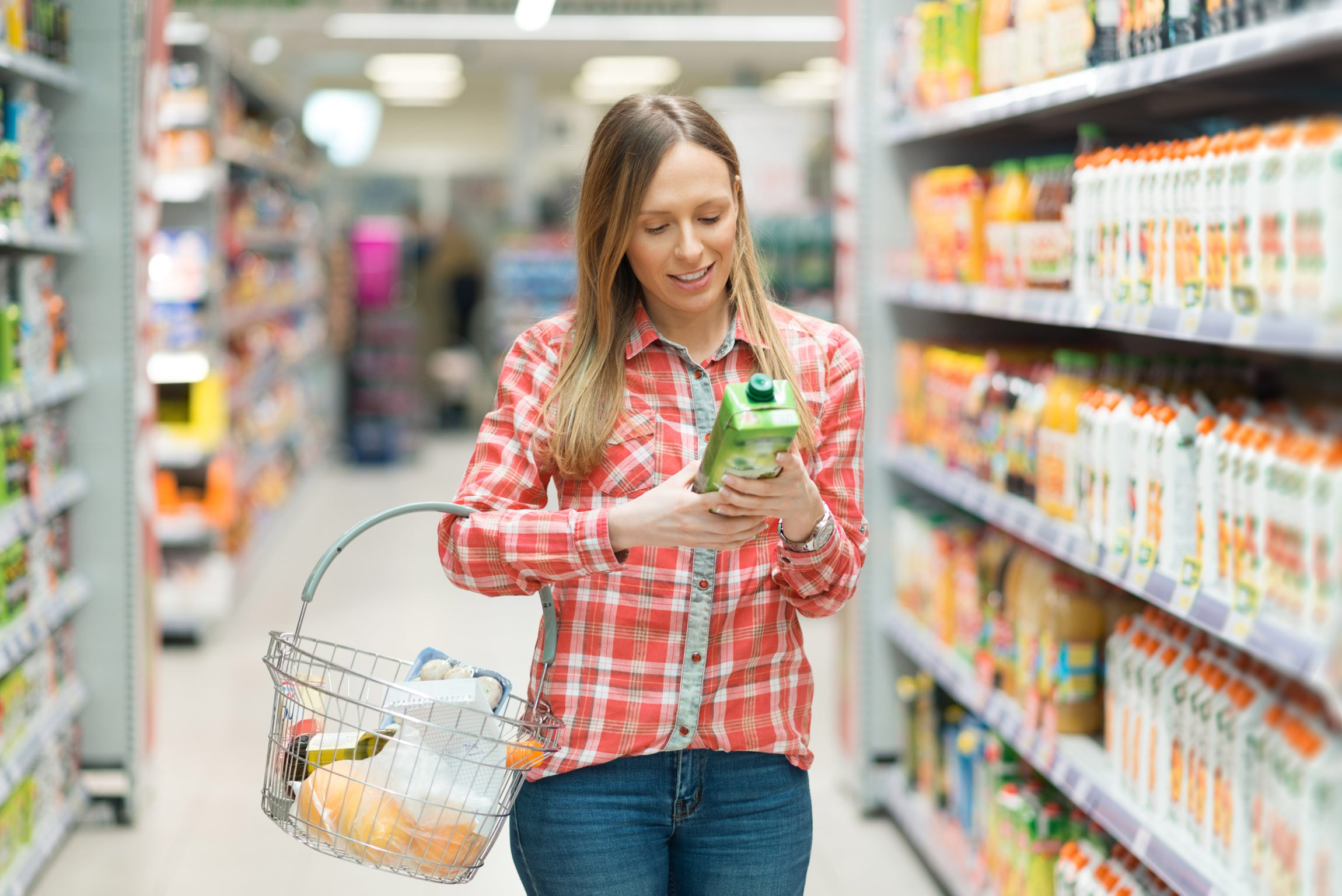 A woman shopping in a grocery store and reading a label