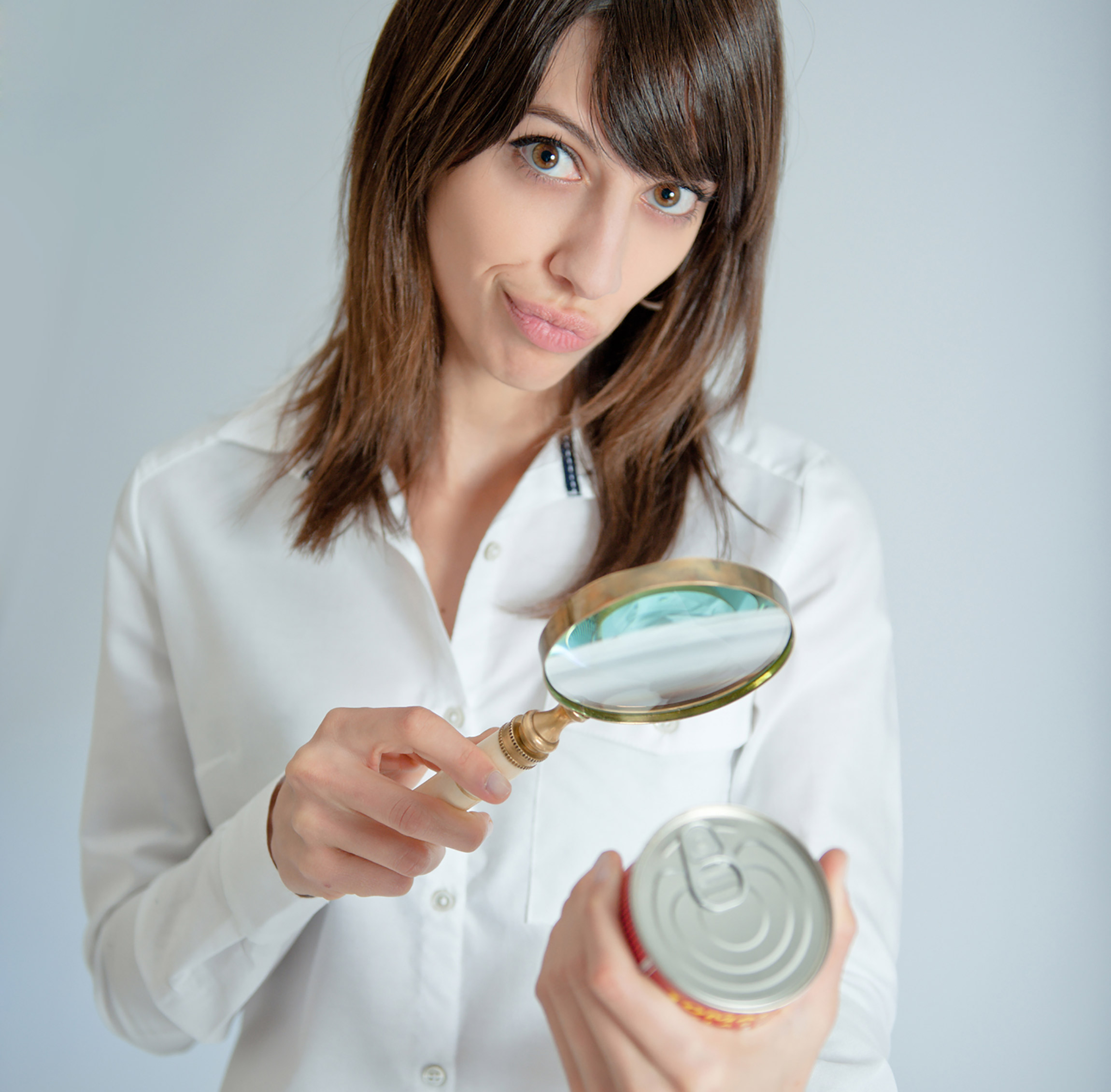A woman inspecting a can's label with a magnifying glass