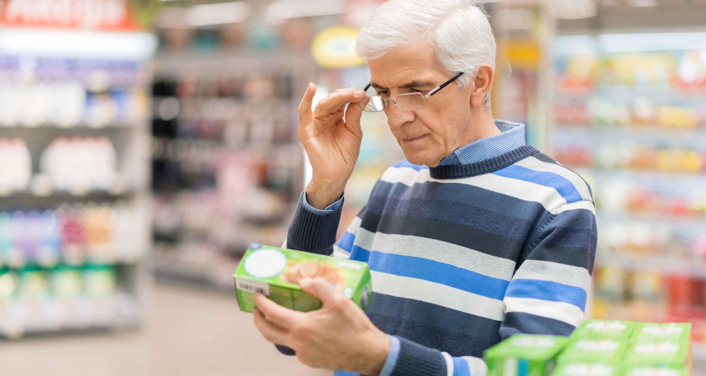 A man in a grocery store reading a food item's label