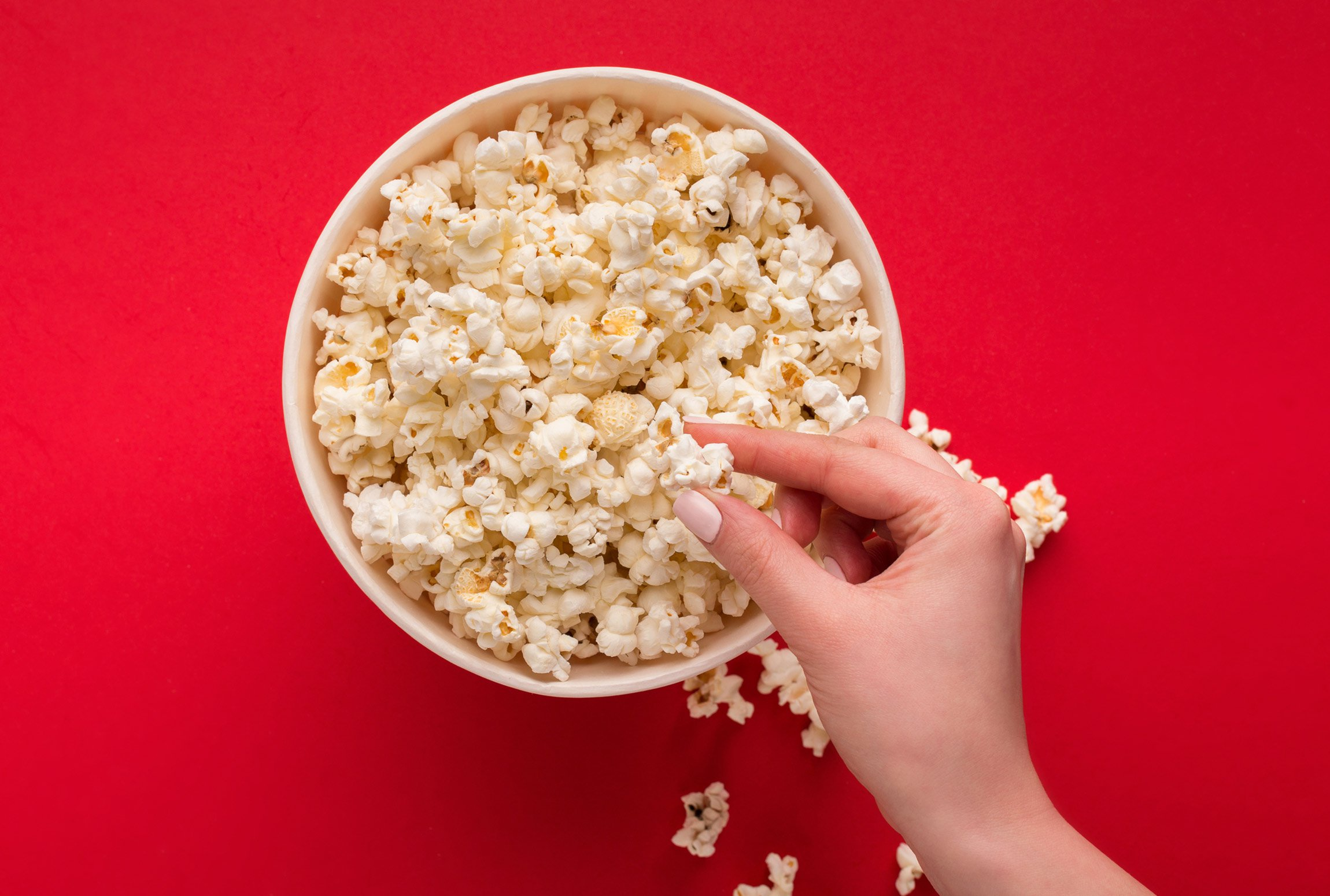 A hand taking popcorn out of a bowl