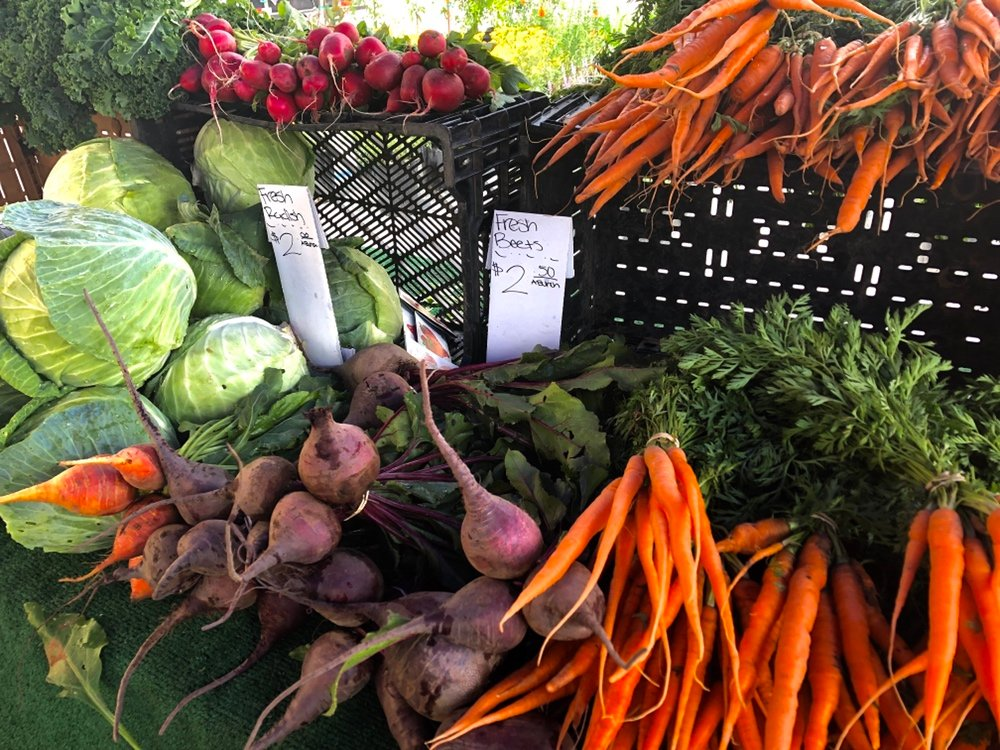 A variety of vegetables in a booth at a farmers' market