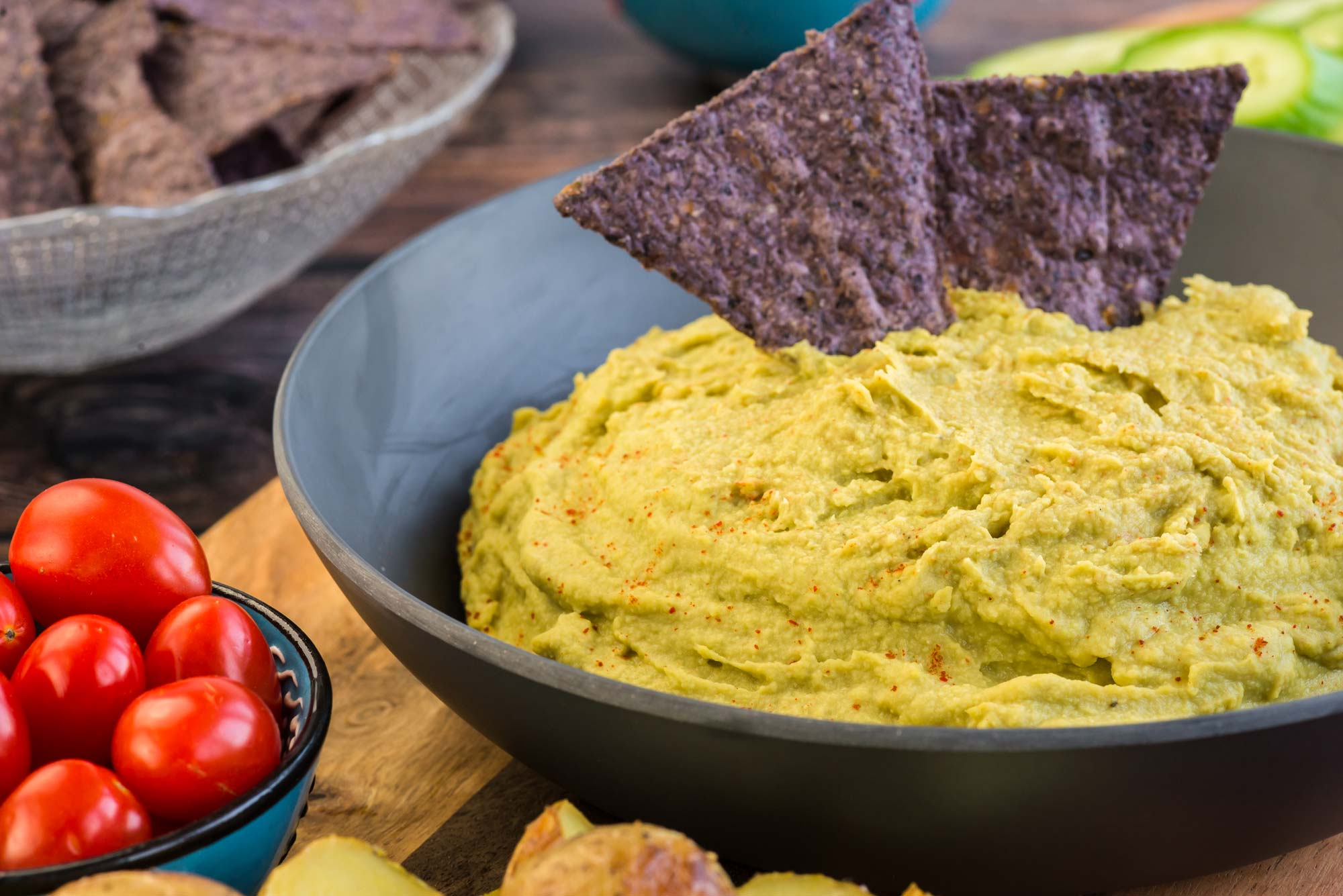 green pea hummus in bowl with chips