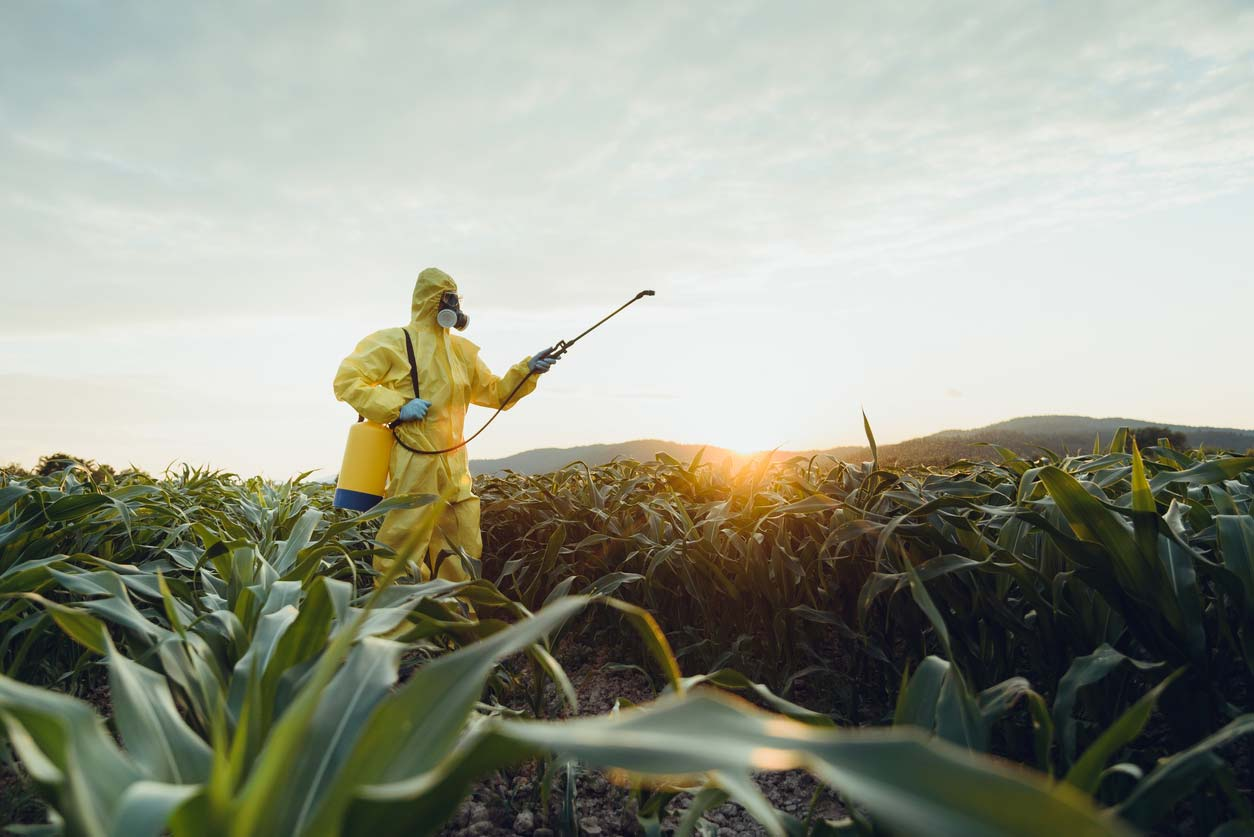 man in hazmat suit spraying crops with pesticides