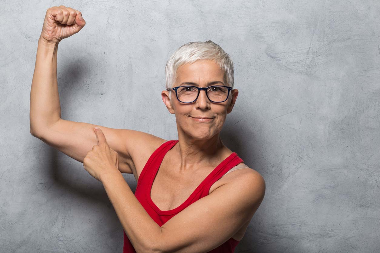 elderly woman showing off her arm muscles