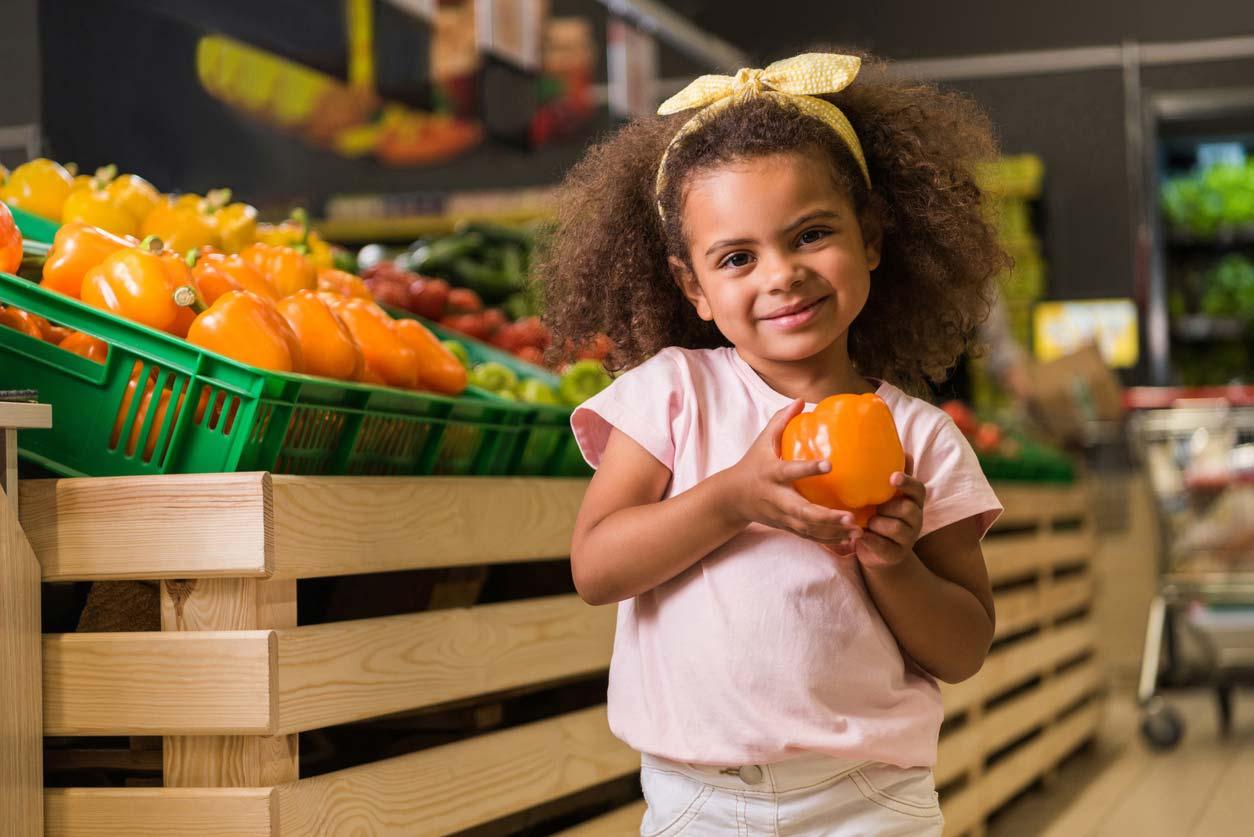 little girl holding bell pepper in grocery store