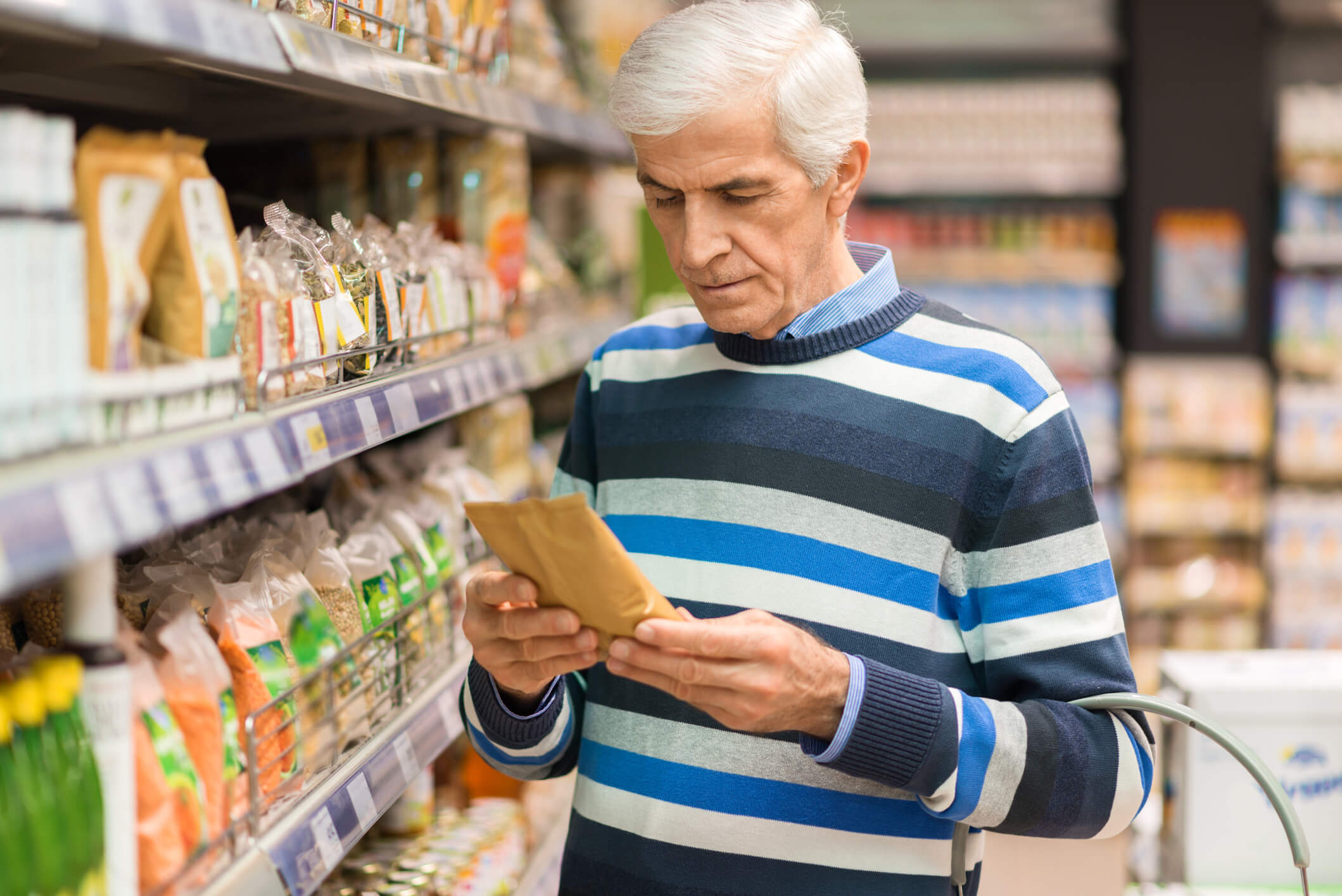 Older man examining nutrition label in grocery store
