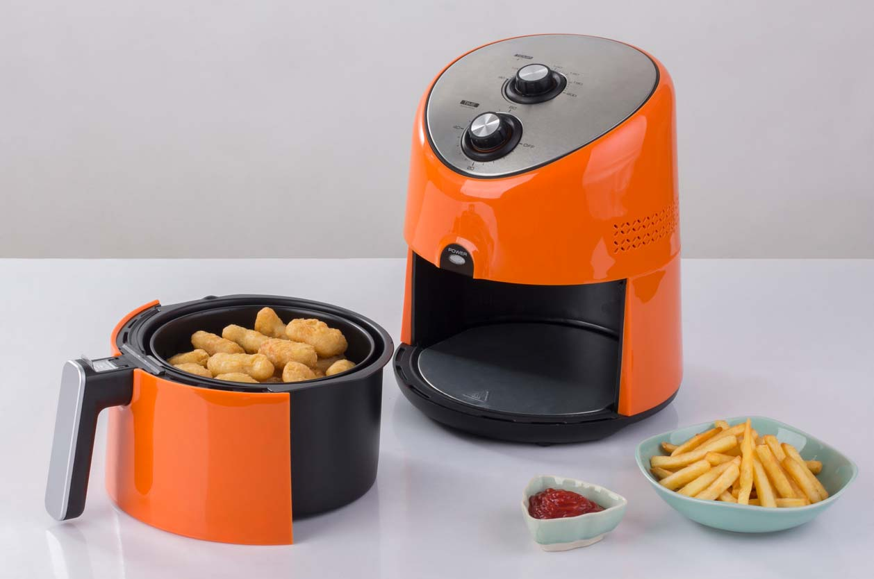 bright orange air fryer on counter with food