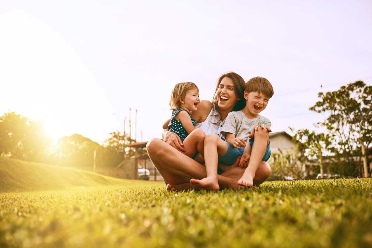 Mother laughing with two children on the grass