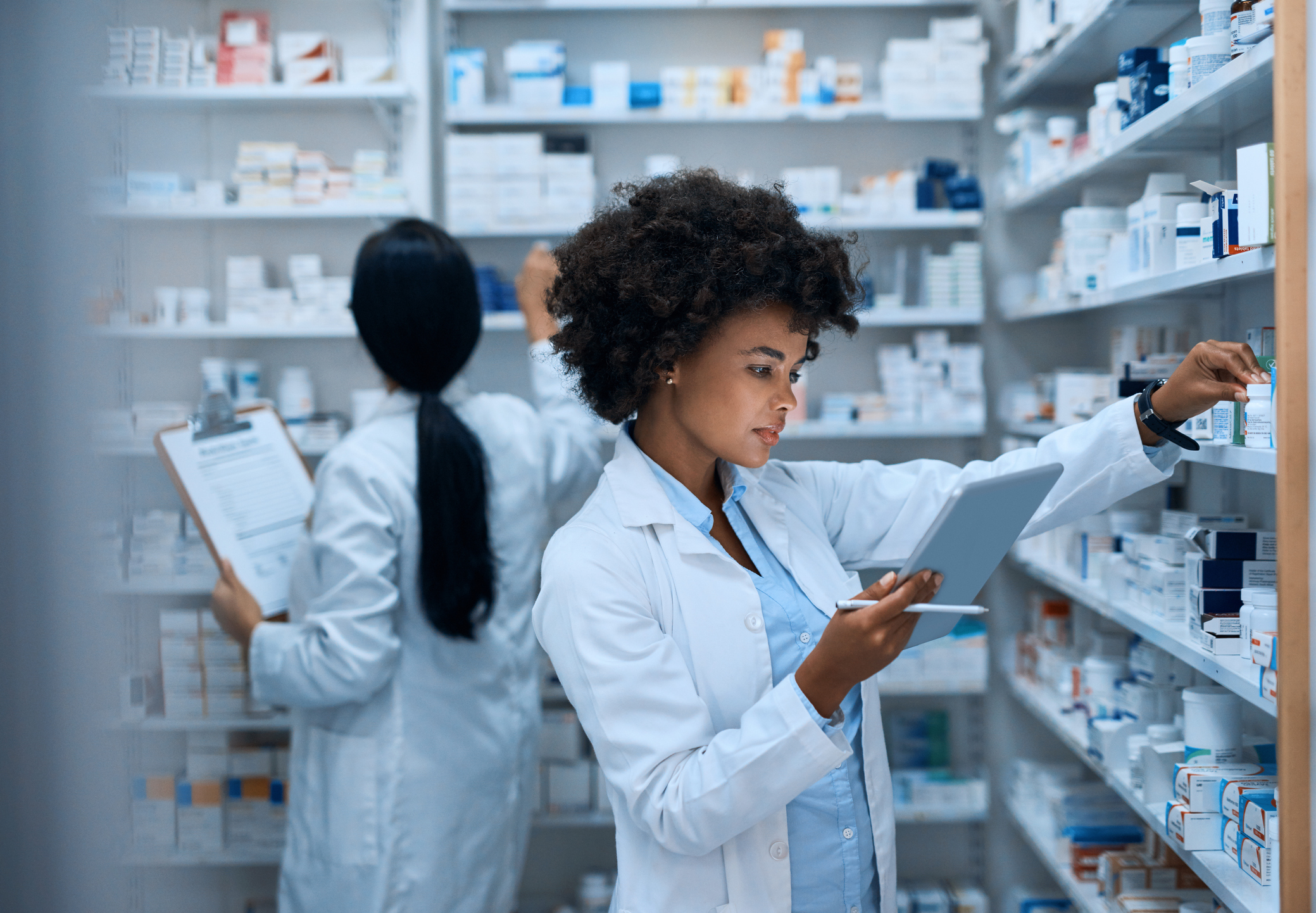 Shot of a young woman doing inventory in a pharmacy on a digital tablet with her colleague in the background