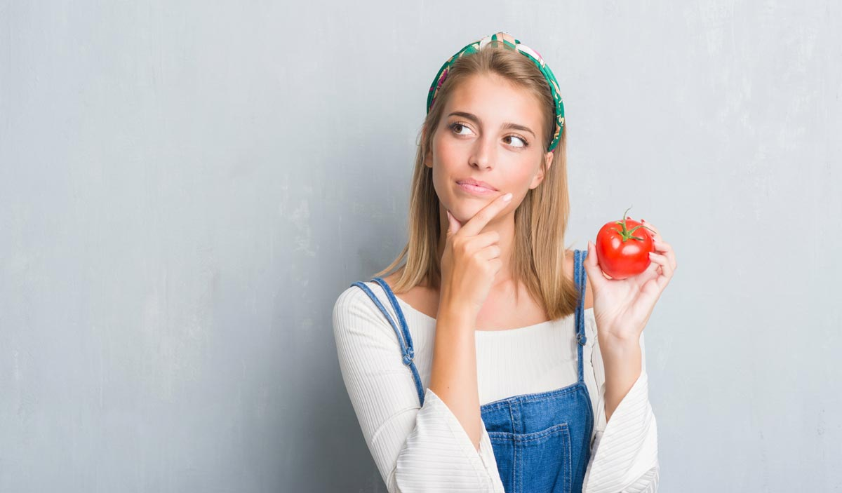 thoughtful woman holding tomato