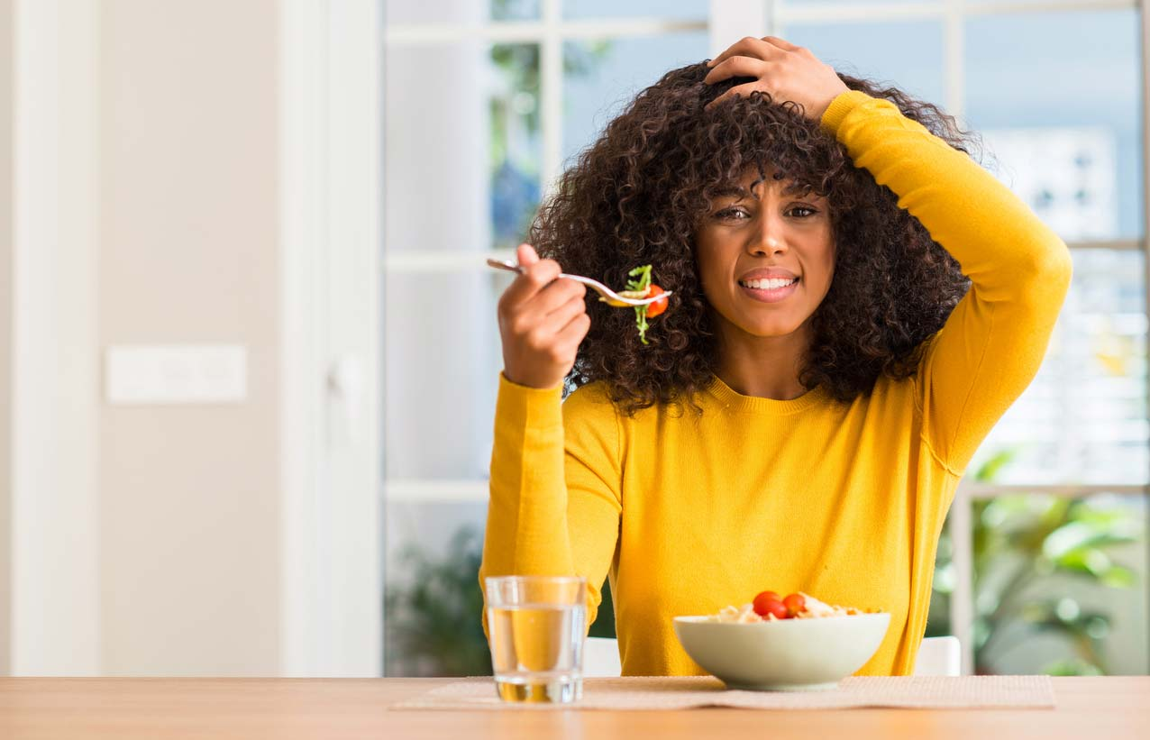 woman showing stress while eating food with tomatoes