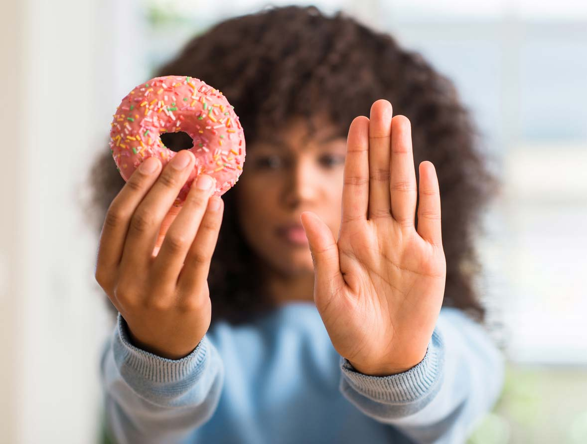 Woman holding up donut and hand to not eat it