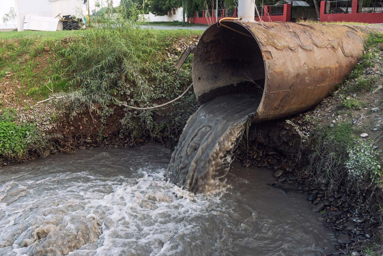 dirty sewage water pouring into drainage ditch