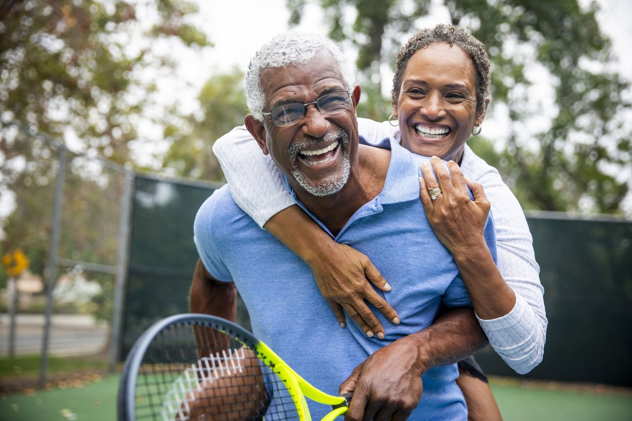 senior couple piggy-back on tennis court