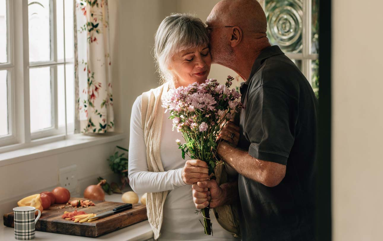 senior couple at home exchanging flower gift
