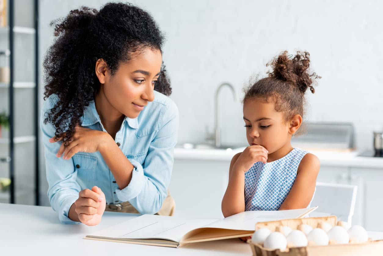 Mother and daughter looking at cookbook together with eggs on counter.