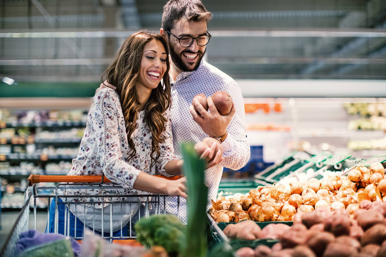 couple in supermarket doing holiday meal planning