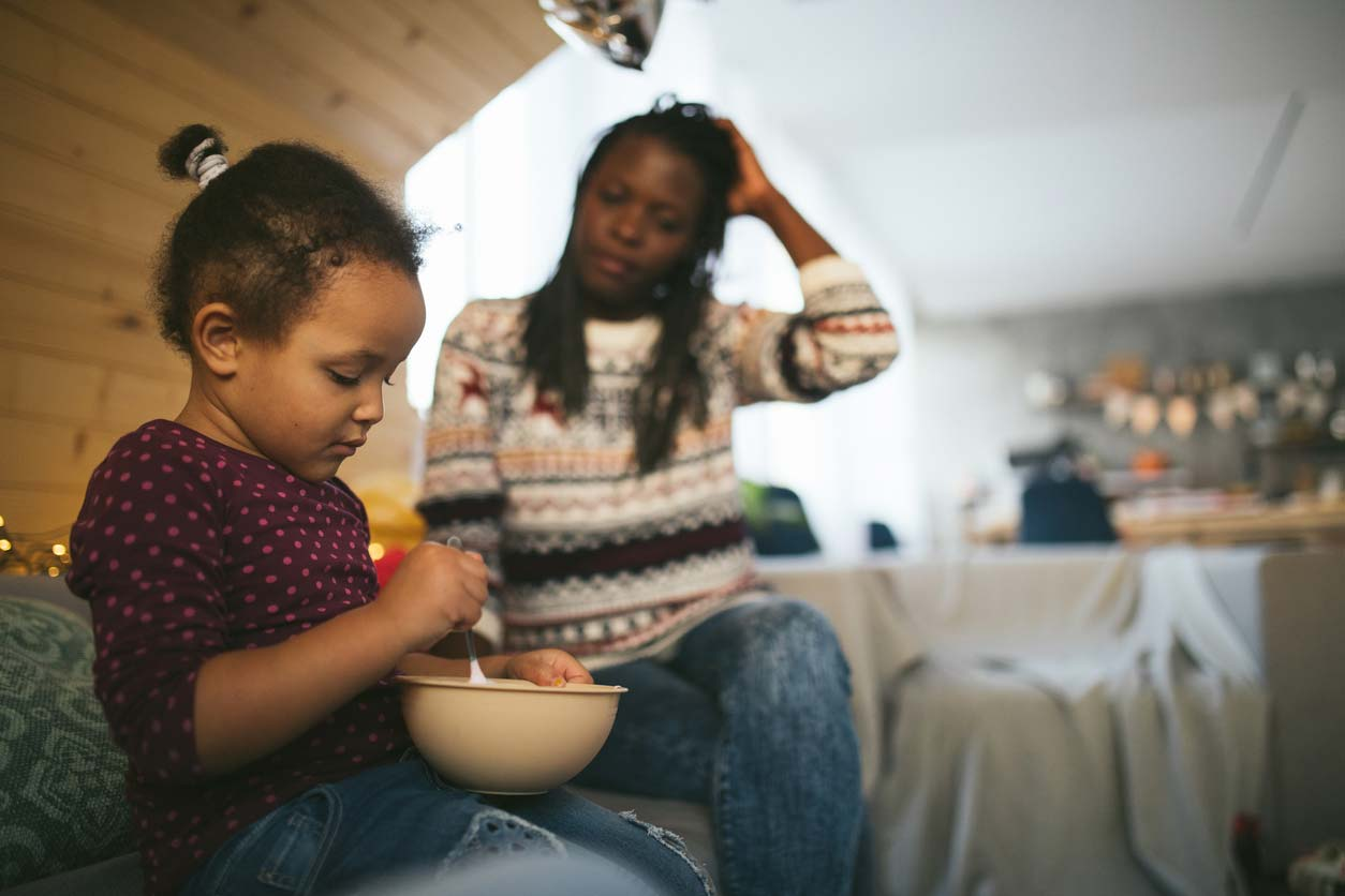 Daughter with bowl of food and worried mom