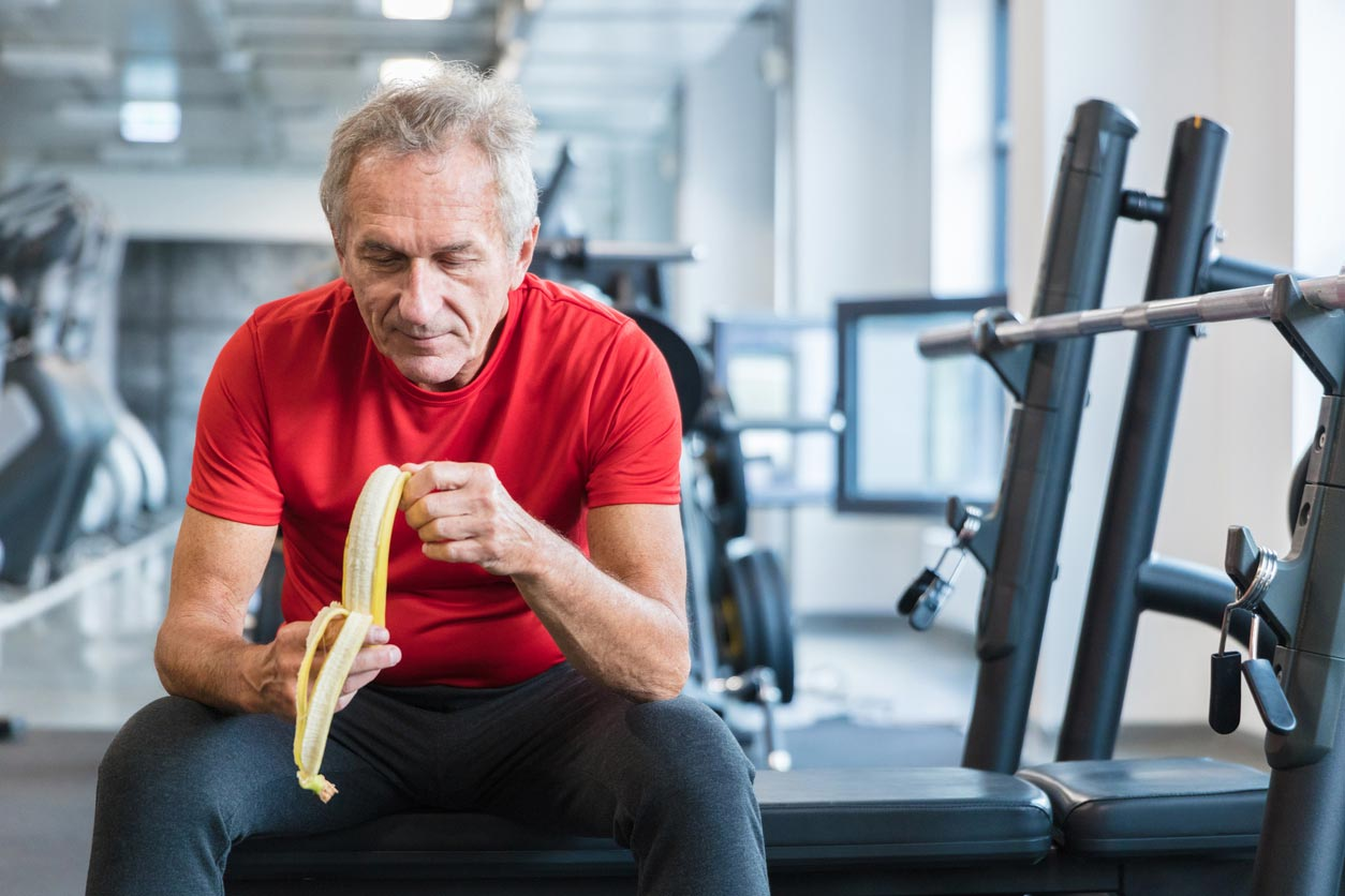 senior man eating banana in weight room