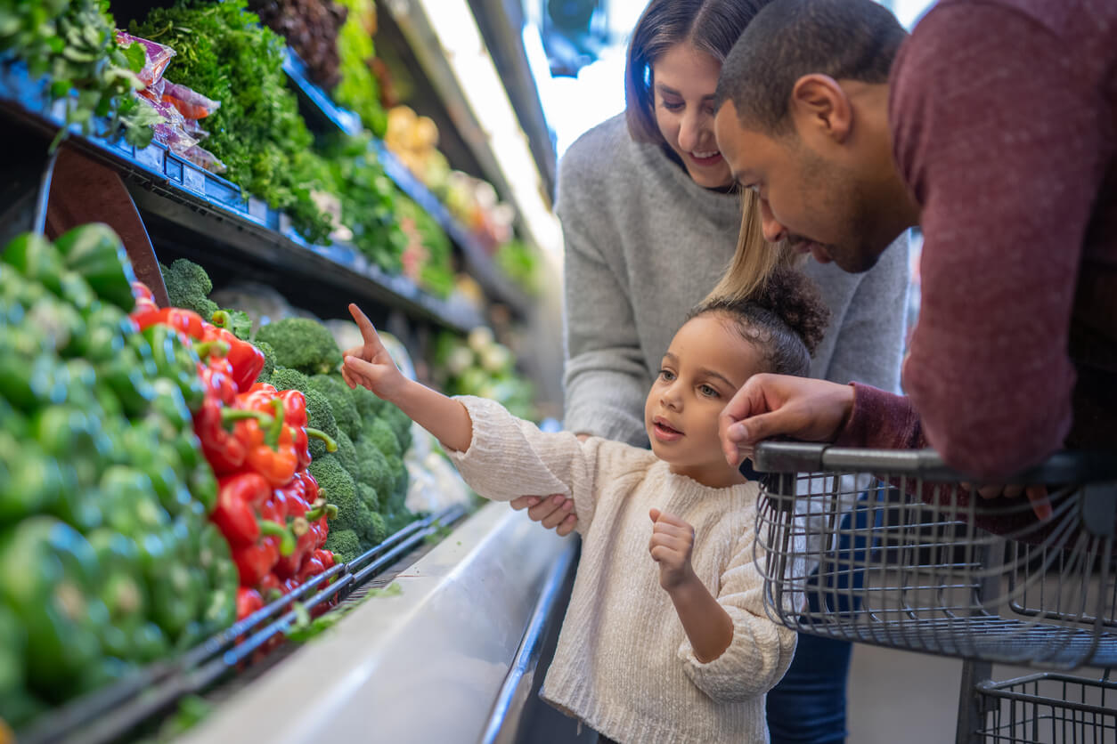 mixed race couple grocery shopping with their preschool age daughter