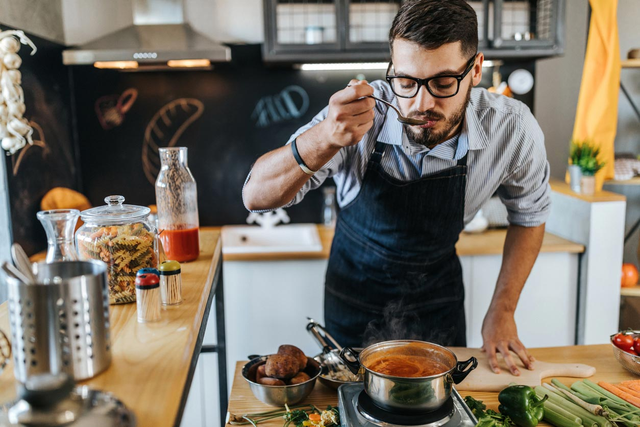 man tasting food while cooking