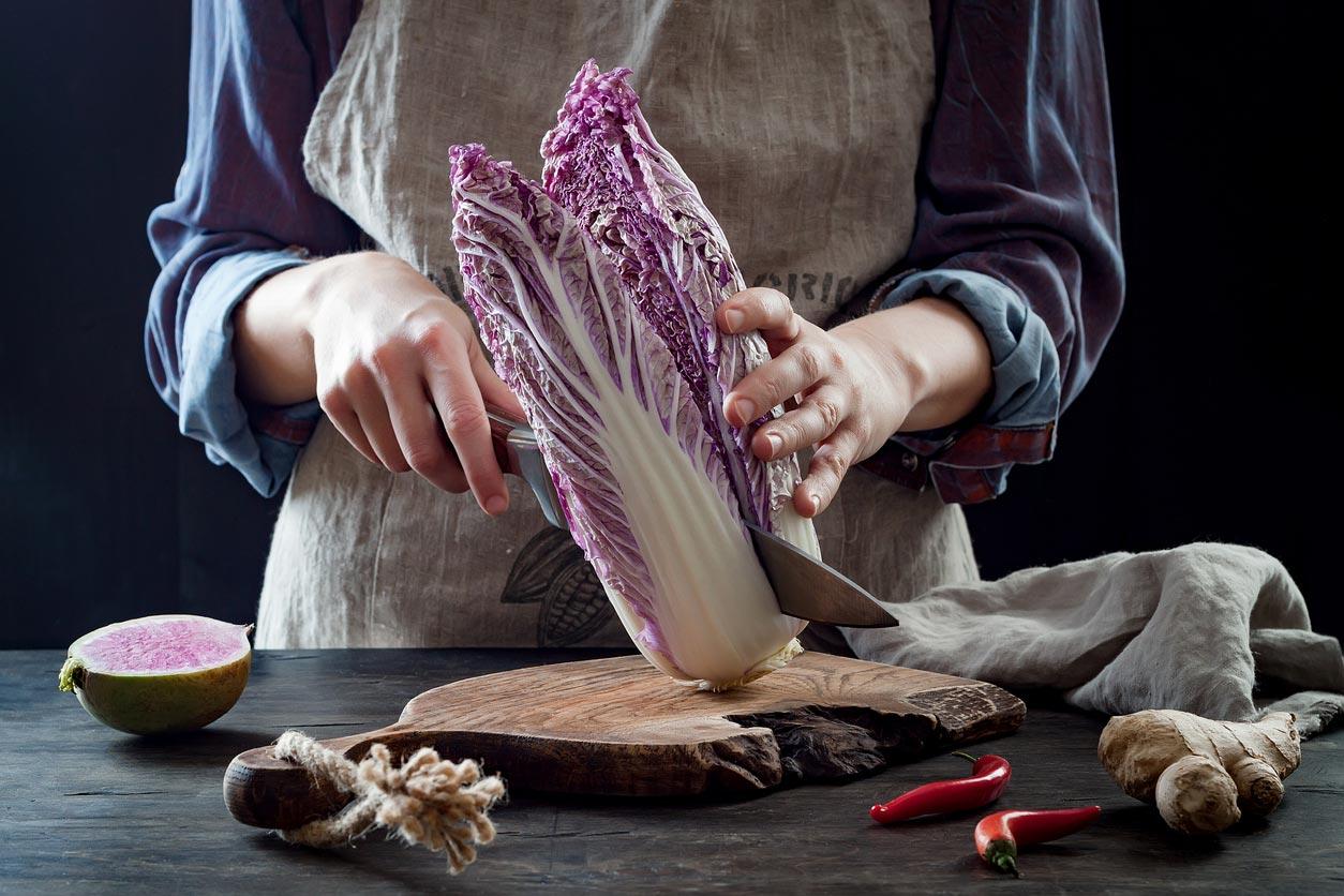 woman cutting purple cabbage